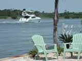 Two green Adirondak chairs behind which is a yacht on the Intracoastal Waterway.