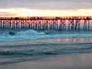 an ocean sunrise as seen through the pilings of the pier at Flagler Beach, Florida
