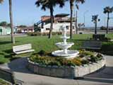 a three-tiered fountain and benches in Veteran's Park with a palm tree and ocean backdrop